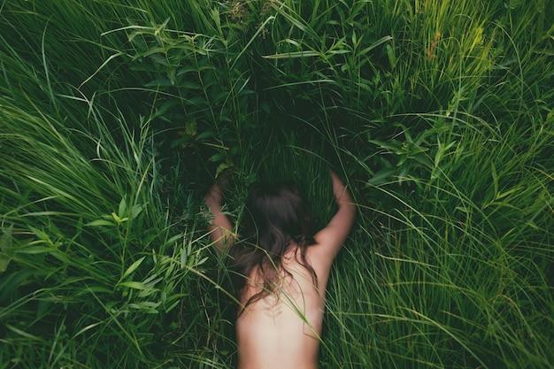 Молодая девушка лежит на животе и обнимает траву руками. Premium Фотографии