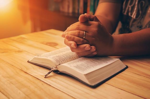Христианская рука во время молитвы и поклонения христианской религии Premium Фотографии