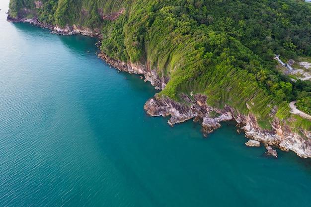 海の波、ビーチ、岩の多い海岸線と美しい森の空中のトップビュー。 Premium写真