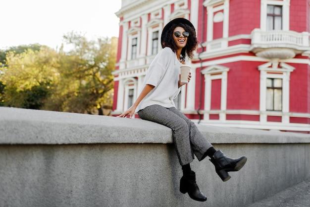橋の上に座って楽しんでいるアフロの髪の黒人女性。革のブーツと流行のズボンを身に着けています。旅行気分。古いヨーロッパの都市での幸せな余暇。 無料写真