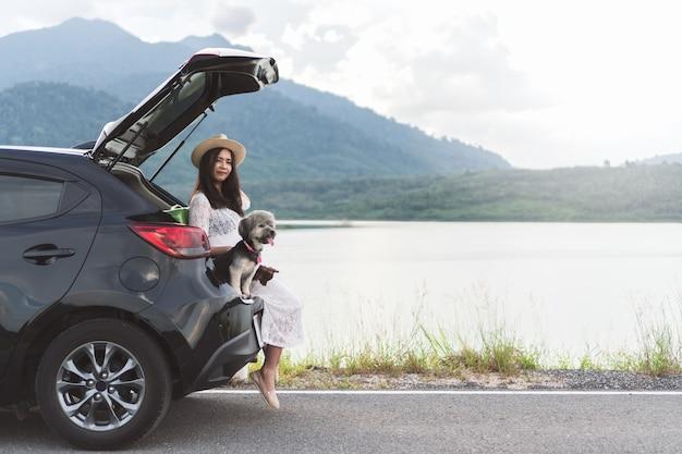ハワイの若い女性旅行者は湖と夕日で犬とハッチバック車に座っている。 Premium写真