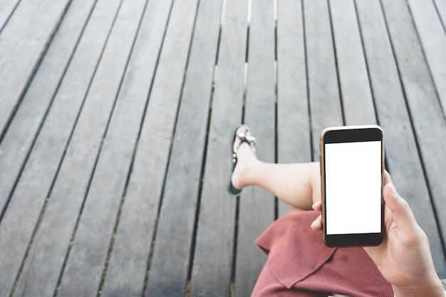 空白の白いデスクトップ画面で黒いスマートフォンを持っている女性の手のモックアップ画像。 Premium写真