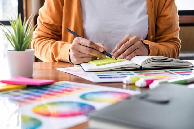 色の選択とグラフィックタブレットでの描画に取り組んでいる創造的なグラフィックデザイナーのイメージ Premium写真