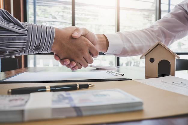 Агент по недвижимости и клиент пожимают друг другу руки после подписания контрактных документов на покупку недвижимости Premium Фотографии