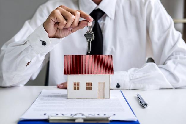 Агент по недвижимости менеджер по продажам держит ключи клиента после подписания аренды Premium Фотографии