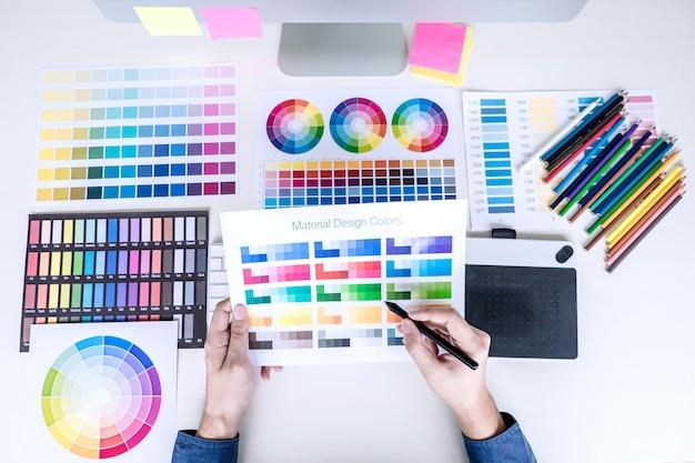 Мужской креативный графический дизайнер работает над выбором цвета и образцами цветов Premium Фотографии