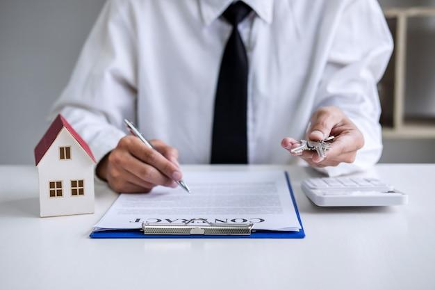 Менеджер по продажам держит ключи у клиента после подписания договора аренды Premium Фотографии