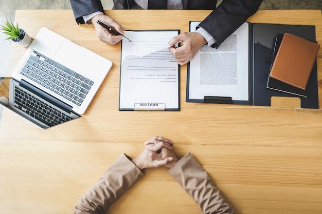 Совет читает резюме во время собеседования, работодатель берет интервью у молодой женщины, ищущей работу Premium Фотографии