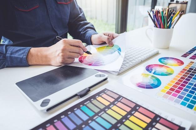 Креативный графический дизайнер, работающий над выбором цвета и нанесением на графический планшет на рабочем месте Premium Фотографии