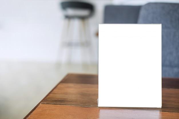 コーヒーショップのテーブルの上の空白のメニューフレームは、あなたのテキストを表す Premium写真
