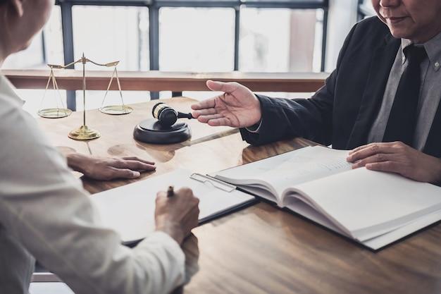 男性の弁護士または裁判官が、ビジネスウーマンクライアント、法律および司法サービスとのチーム会議を開催します。 Premium写真
