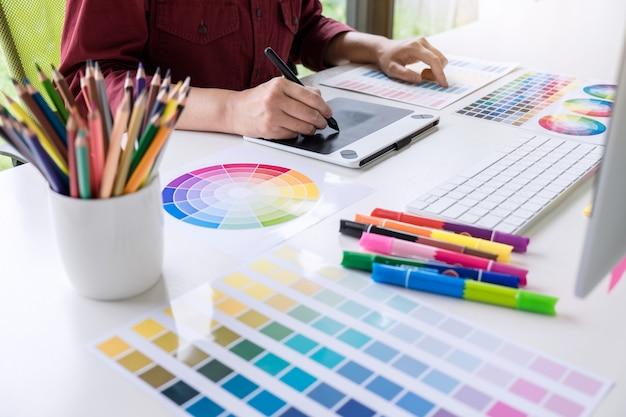 Изображение женского творческого графического дизайнера, работающего над выбором цвета и опирающегося на графический планшет Premium Фотографии