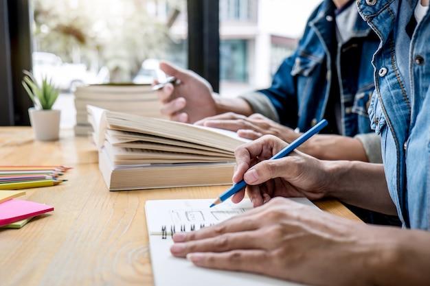 Преподаватель средней школы или группа студентов колледжа, сидящая за столом в библиотеке, занимающаяся изучением и чтением, делающая домашнюю работу и урок, готовит экзамен к поступлению, образование, преподавание, концепция обучения Premium Фотографии