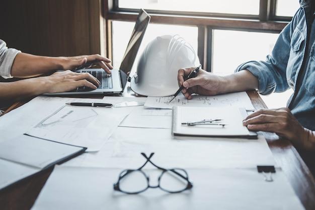 エンジニアチームワーク会議、モデル構築および作業現場でのエンジニアリングツールに関するパートナーと協力するプロジェクトの青写真会議に取り組む図面、建設および構造の概念 Premium写真