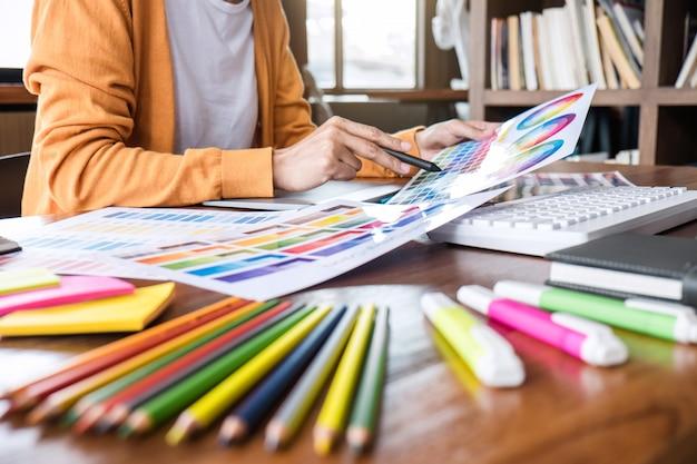 Изображение женского творческого графического дизайнера, работающего над выбором цвета, и графического планшета на рабочем месте с рабочими инструментами и принадлежностями Premium Фотографии