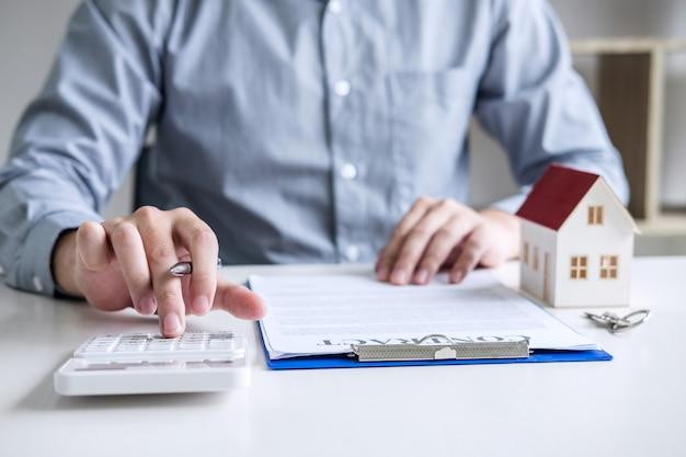 Бизнесмен работает, делая финансы и расчет стоимости инвестиций в недвижимость Premium Фотографии