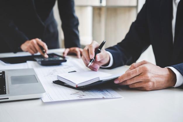 Бизнес коллег, работающих с ноутбуком, обсуждения и анализа графика фондового рынка Premium Фотографии