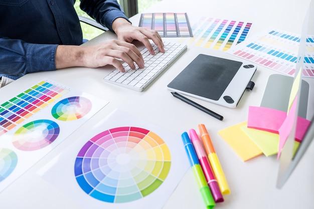 色の選択と色見本に取り組んでいる男性の創造的なグラフィックデザイナー Premium写真