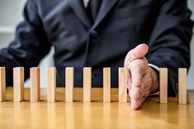 ビジネスマンの手が倒れた木製ドミノ効果を停止またはリスクの連続からの影響 Premium写真