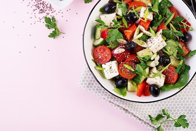 Греческий салат с огурцом, помидорами, сладким перцем, листьями салата, зеленым луком, сыром фета и оливками с оливковым маслом Premium Фотографии