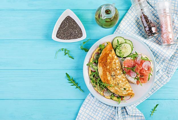 Омлет с редькой, зеленой рукколой и бутерброд с лососем на белой тарелке Premium Фотографии