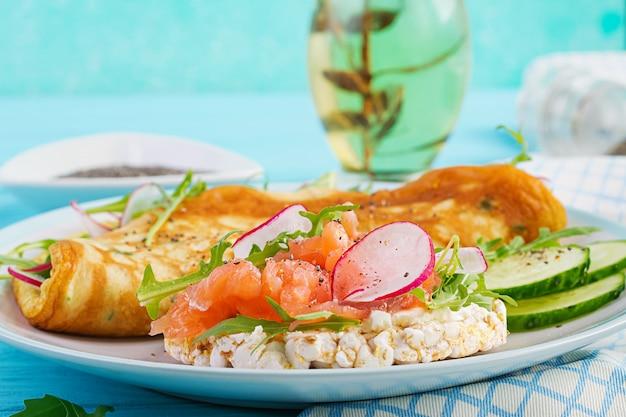 大根、緑のルッコラ、白い皿にサーモンのサンドイッチオムレツ Premium写真