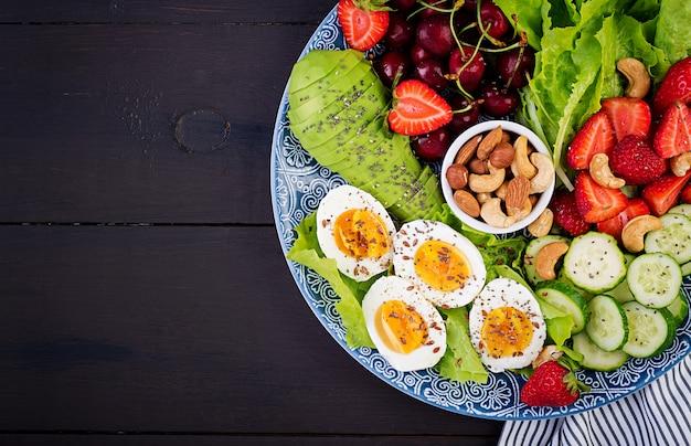 ゆで卵、アボカド、キュウリ、ナッツ、チェリー、イチゴ Premium写真