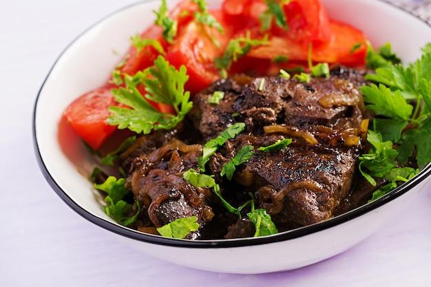 Жареная или жареная говяжья печень с луком и салатом из помидоров Бесплатные Фотографии