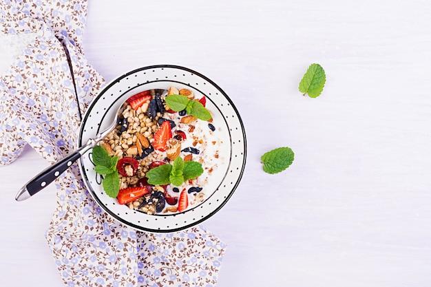 Гранола, клубника, вишня, жимолость, орехи и йогурт в миске Бесплатные Фотографии