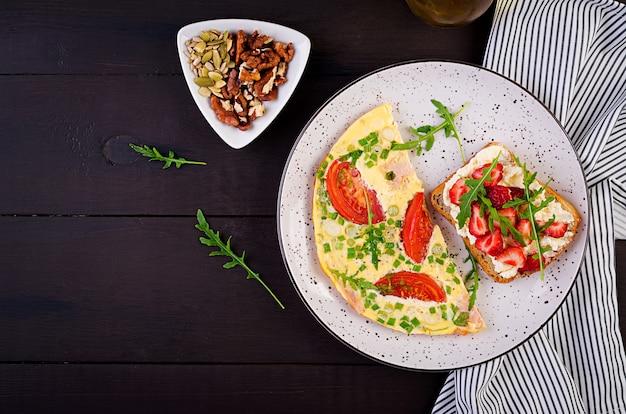 暗いテーブルの上のイチゴ、トマト、ハム、ネギ、サンドイッチのオムレツ Premium写真