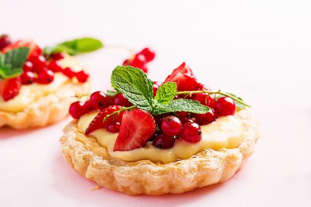 ミントの葉で飾られたイチゴ、スグリ、ホイップクリームのタルト 無料写真
