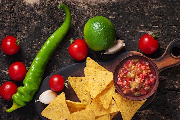 メキシコのナチョチップと木製のボウルにサルサのディップ 無料写真