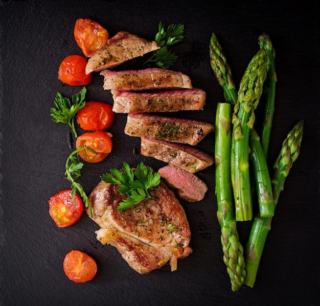 ジューシーなステーキミディアムレアビーフとスパイスとトマト、アスパラガス。上面図 無料写真
