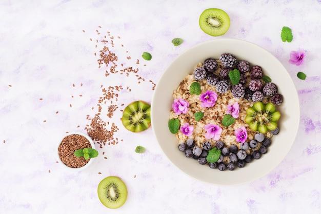 フルーツ、ベリー、亜麻の種子が入ったおいしいヘルシーなオートミールポリッジ。健康的な朝食。フィットネス食品。適切な栄養。 無料写真