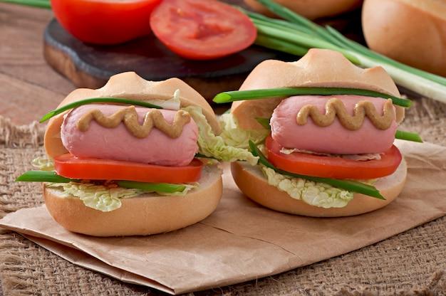 ソーセージとトマトの小さな陽気なホットドッグ 無料写真