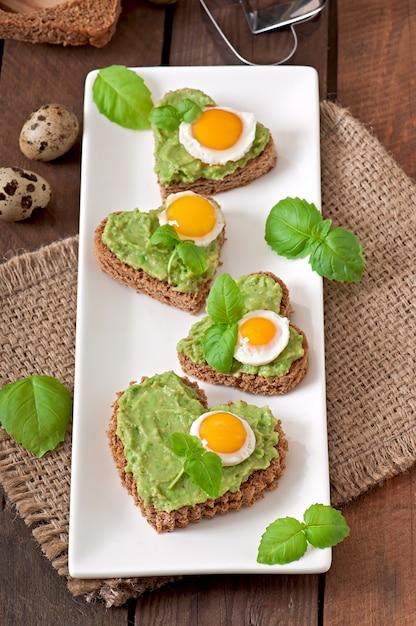 Бутерброд с пастой из авокадо и яйцом в форме сердца Premium Фотографии