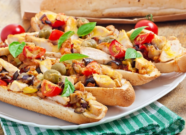 Большой бутерброд с жареными овощами (цуккини, баклажаны, помидоры) и курицей с сыром и базиликом на старых деревянных фоне Premium Фотографии