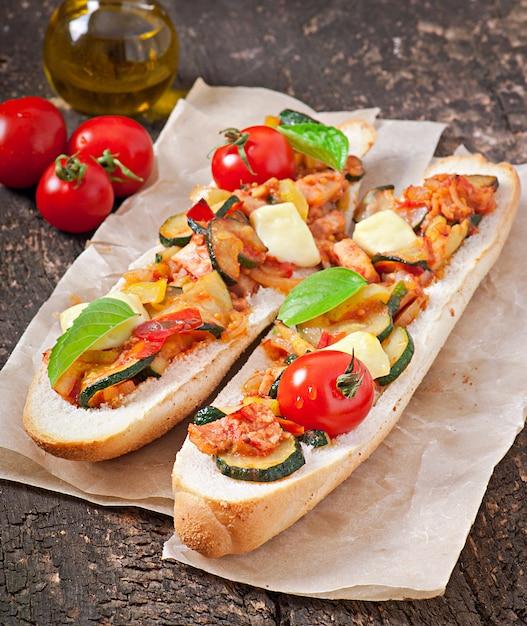 Большой бутерброд с жареными овощами (цуккини, паприка, помидоры) с сыром и базиликом на старых деревянных фоне Premium Фотографии