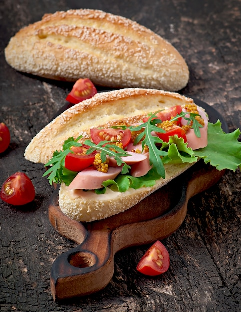 古い木製の背景にソーセージ、レタス、トマト、ルッコラのサンドイッチ Premium写真