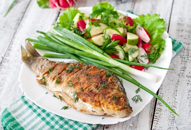 Карп из жареной рыбы и салат из свежих овощей Premium Фотографии