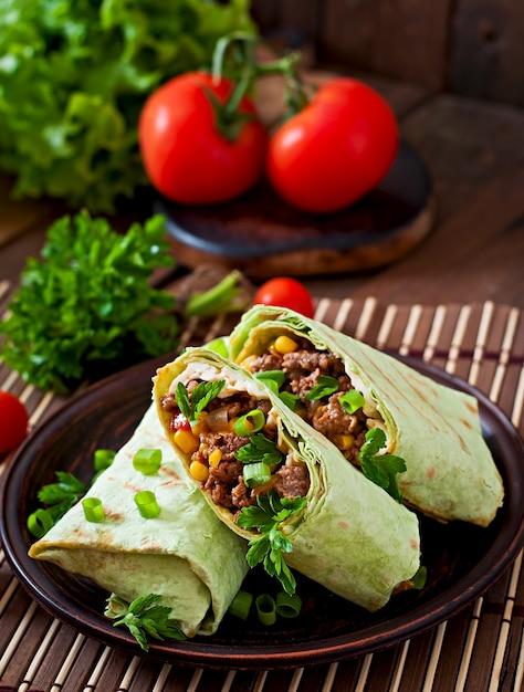 Обертывания буррито с рубленой говядиной и овощами на деревянном фоне Premium Фотографии