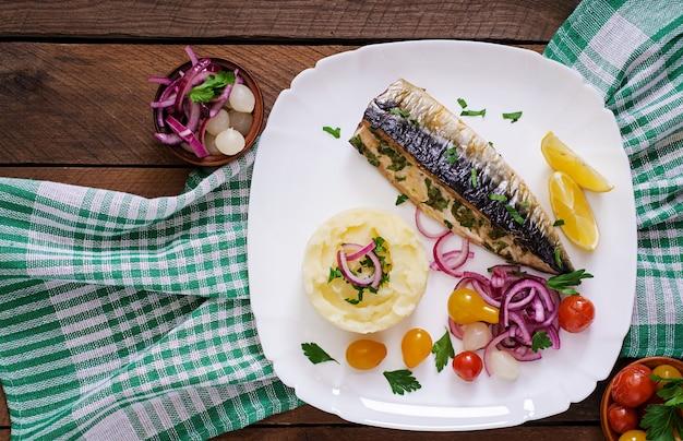 Запеченная скумбрия с зеленью и гарниром из картофельного пюре и маринованных овощей. вид сверху Premium Фотографии