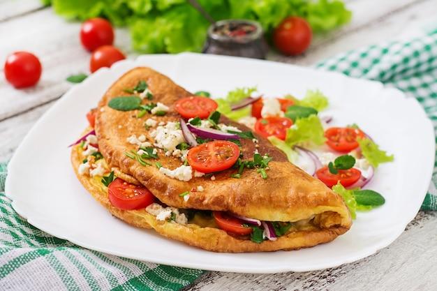 白い皿にトマト、パセリ、フェタチーズのオムレツ。 Premium写真