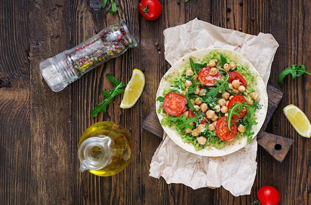 ワカモレ、ひよこ豆、トマト、ルッコラのビーガンタコス。健康食品。便利な朝食。平干し。上面図 Premium写真