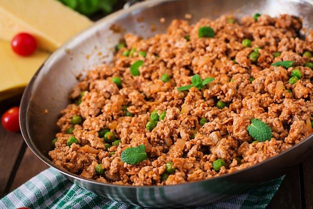 Фарш из мяса на сковороде для фарширования лазаньи. Premium Фотографии