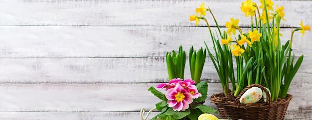 イースターエッグと明るい木製のテーブルの花 Premium写真