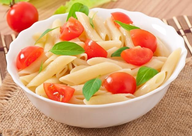 Салат из макарон с помидорами черри и свежими листьями базилика Бесплатные Фотографии