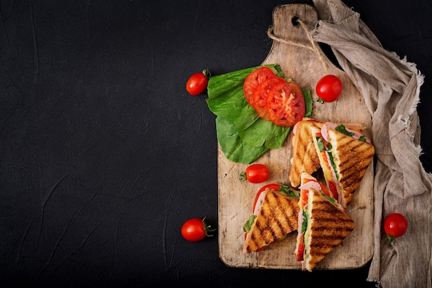 Клубный сэндвич-панини с ветчиной, томатом, сыром и базиликом. квартира лежала. вид сверху Premium Фотографии