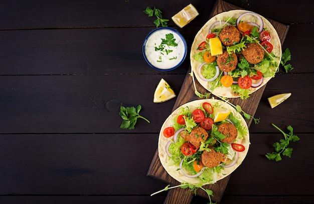 ファラフェルと新鮮なサラダのトルティーヤラップ。ビーガンタコスベジタリアンの健康食品。上面図 無料写真