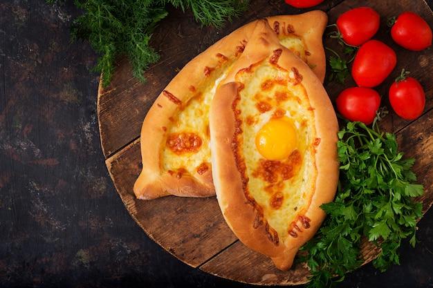 アジャリアンのハチャプリ。モッツァレラチーズと卵の入ったパイを開けます。グルジア料理。 無料写真